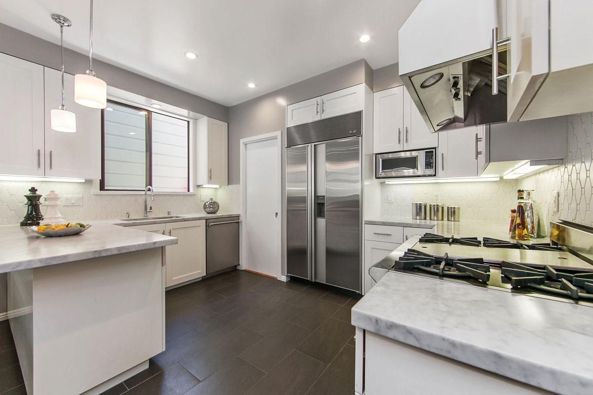Condo Kitchen with Wolf Range, Subzero Refrigerator, Carrara Marble Counters, White Cabinets and Elongated Hexigon backsplash