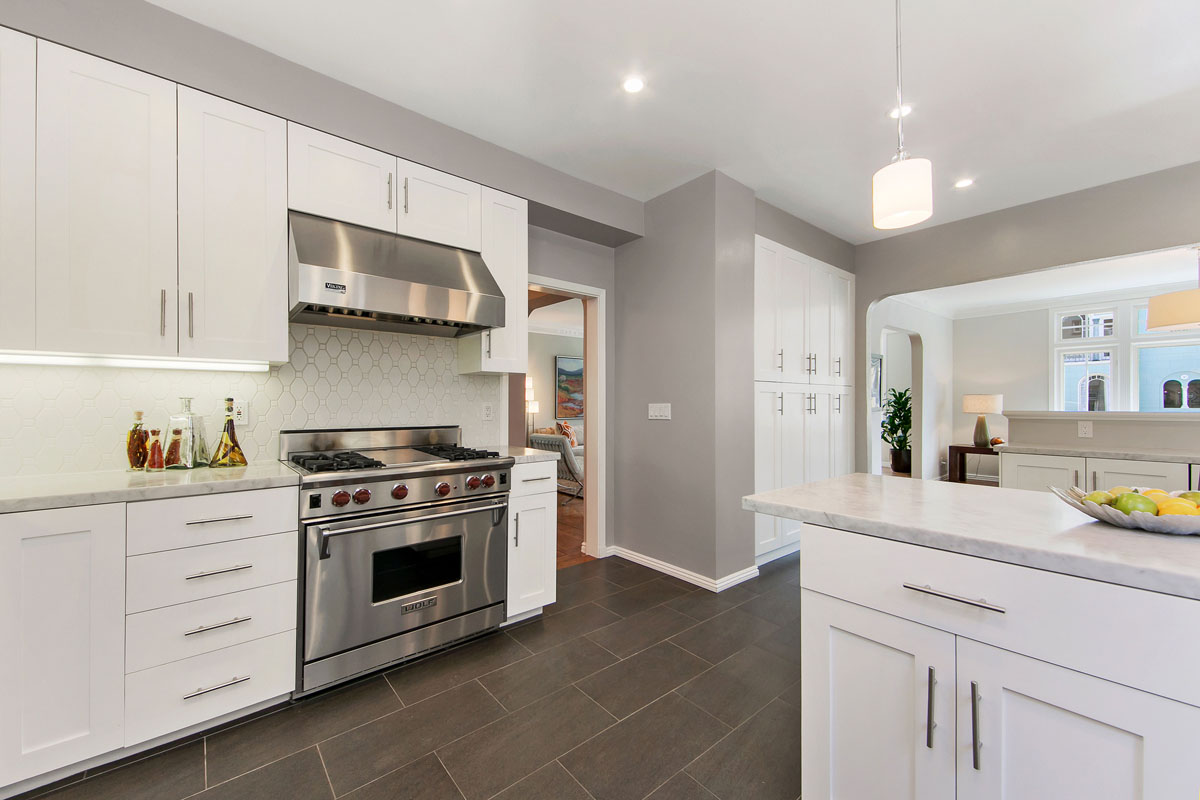 Condo Kitchen with Wolf Range, Subzero Refrigerator, Carrara Marble Counters, White Cabinets and Elongated Hexigon backsplash